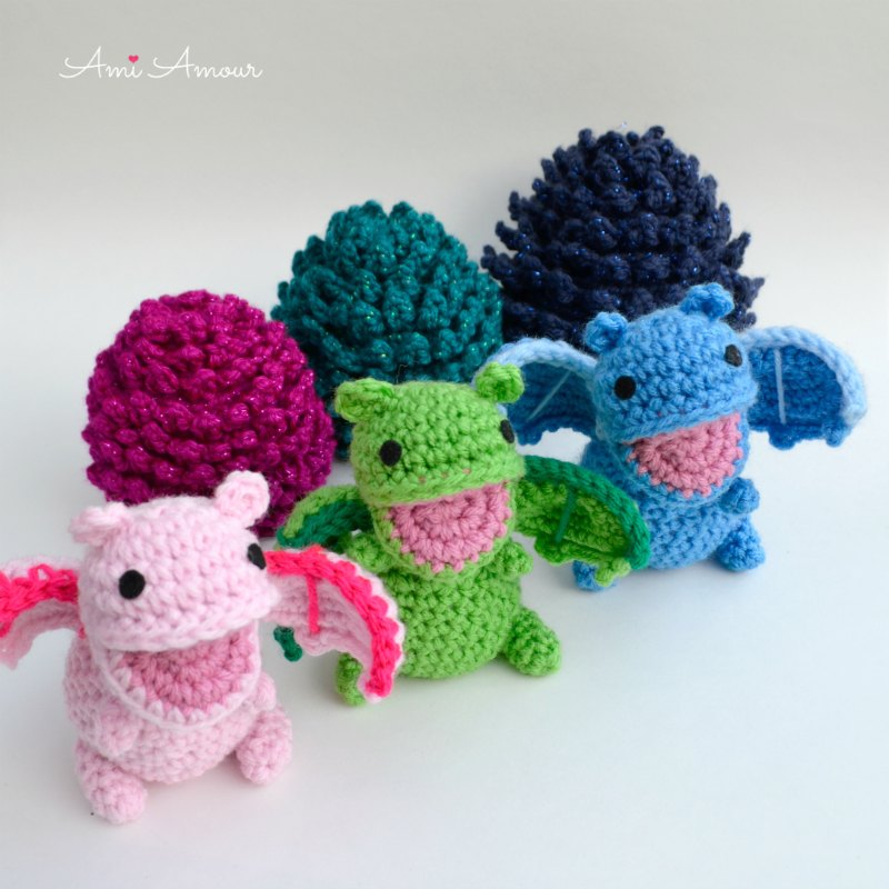 Crochet Dragons standing in front of their Eggs