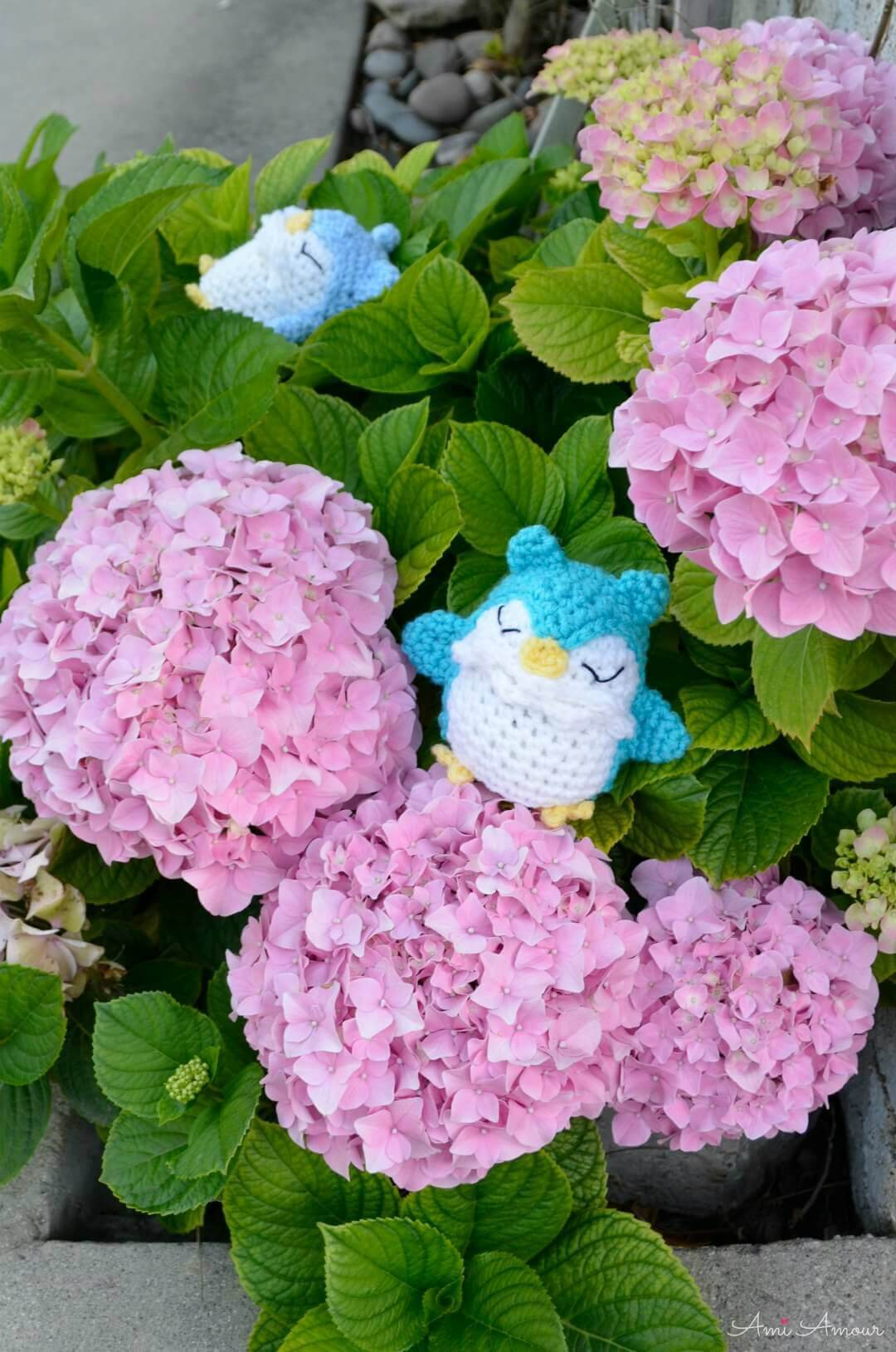 Blue hued Crochet Owls on top a bed of Pink Hydrangeas